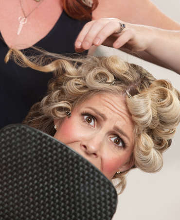 pulling hair: Frightened blond white female with mirror in hair salon
