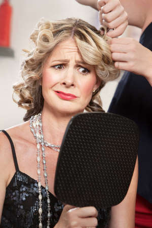Dissatisfied pretty woman in salon holding mirror Stock Photo - 16578031