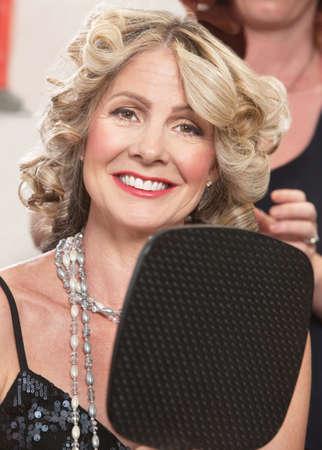 donne mature sexy: Mezza età attraente femmina con specchio parrucchiere