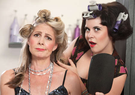 Sad mature woman with mirror and friend in curlers photo