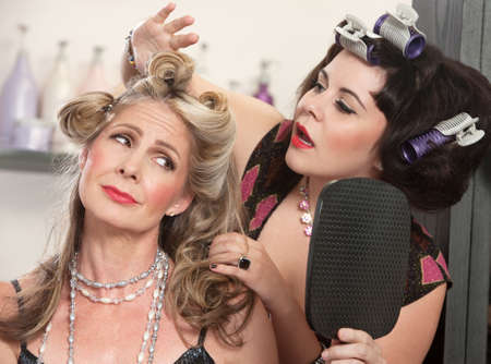 Woman in curlers fixing a woman's bad hairdo Stock Photo - 16578033