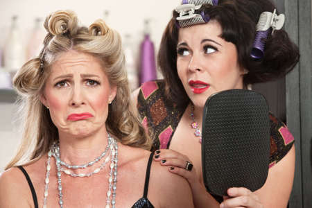 sympathetic: Pouting woman with mirror and sympathetic friend Stock Photo