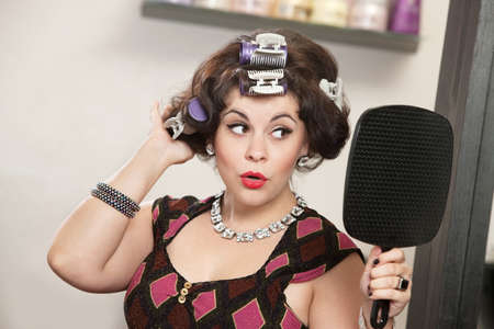 Proud woman in curlers looking in a mirror Stock Photo - 16578058