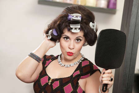 Impressed woman in curlers holding a mirror Stock Photo - 16578057
