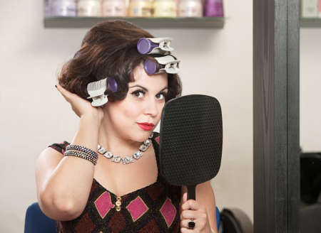 Caucasian woman in curlers with mirror feeling her hair Stock Photo - 16578030