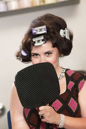 Insecure young white female in curlers behind mirror Stock Photo - 16578075