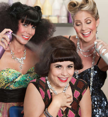 flattered: Three happy women playing with hair spray in beauty salon Stock Photo