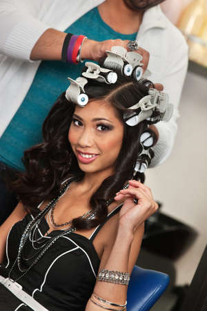 Smiling young woman with hair stylist removing curlers photo