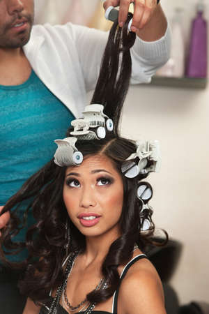 hair dresser: Pretty young woman watching curlers being removed from hair