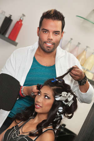 Handsome hair stylist removing womans hair curlers photo