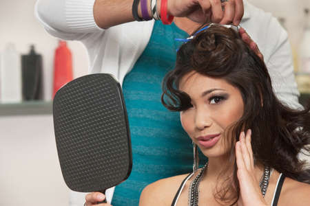 Sexy woman feeling hair and holding mirror as stylist works Stock Photo - 16578073