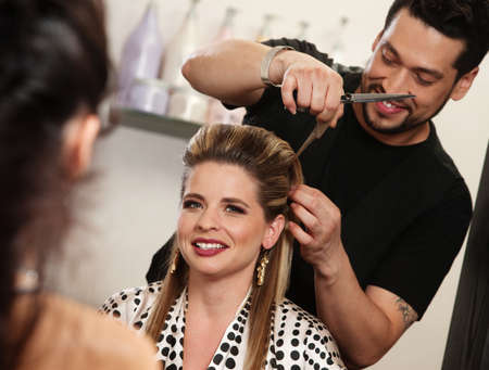 cutting hair: Smiling woman getting haircut by handsome hairdresser Stock Photo