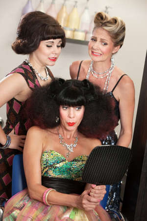Bad hairdo on happy woman and embarrassed friends in salon photo