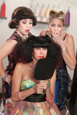 bad hair day: Pouting woman in afro wig with embarrassed friends in hair salon