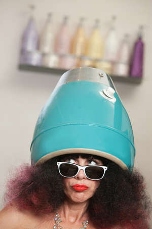 Serious lady looking over with head in hair dryer Stock Photo - 16680520