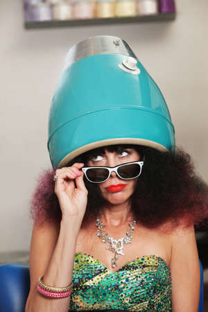 Pouting lady with frizzy hair sitting under hair dryer photo