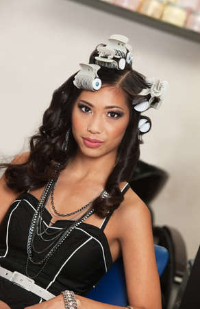Gorgeous young Asian female with hair curlers photo