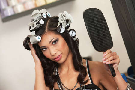curlers: Beautiful Vietnamese lady with hair curlers and mirror Stock Photo