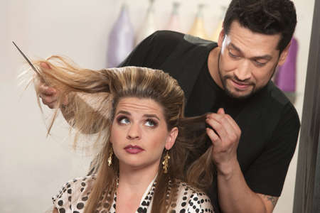 Embarrassed male hair stylist and female customer in salon photo