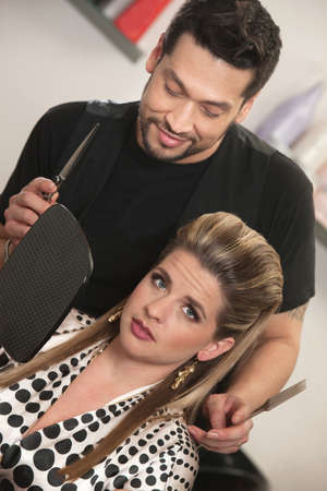 Hairdresser holding mirror for annoyed European customer Stock Photo - 16680539