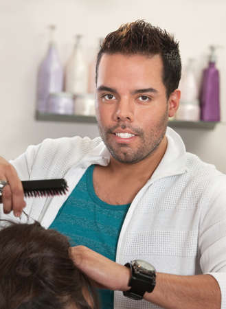Attractive Latino male hair stylist working with hairbrush Stock Photo - 16680518