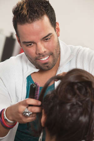 Smiling Latino male hair stylist working with customer Stock Photo - 16680523