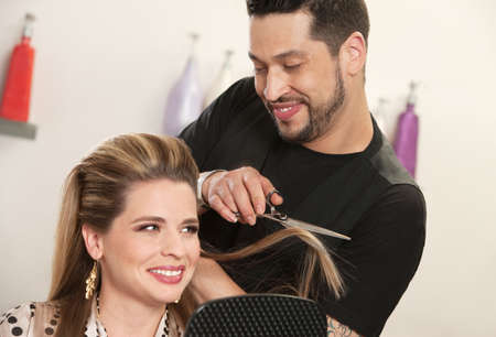 Gorgeous woman getting haircut by attractive Arab hairdresser photo