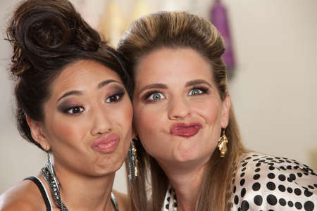 puckering lips: Asian and European pair of women making faces Stock Photo