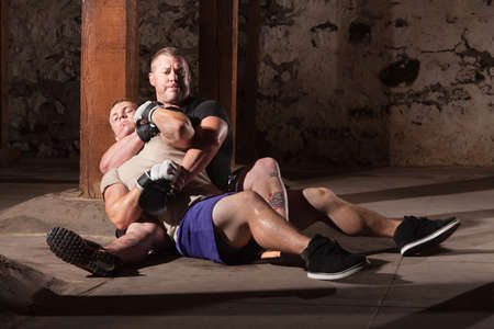 the opponent: Mixed martial artist with opponent in submission choke hold Stock Photo
