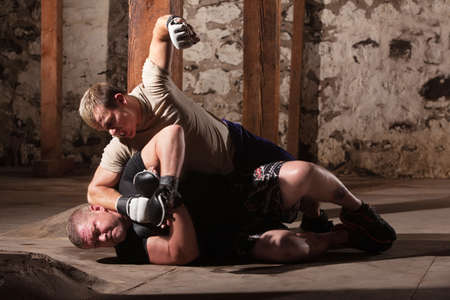 under ground: Aggressive MMA fighter punching opponent on the ground
