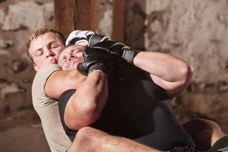 the opponent: European MMA athlete strangles opponent from behind Stock Photo