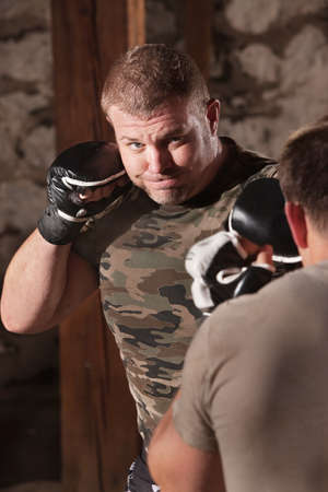 opponent: Strong mixed martial artist jabbing at opponent Stock Photo