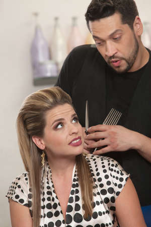 Handsome Latino hairdresser talking with female client photo