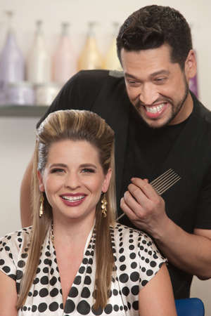flattered: Pretty Caucasian woman and bearded hair stylist smiling Stock Photo