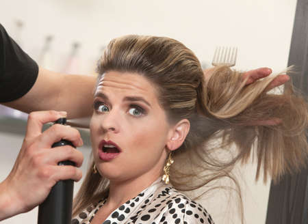 Pretty woman is startled by stylist using hair spray photo