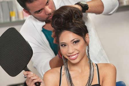 hair stylist: Vietnamese female holding mirror with hairdresser working behind her