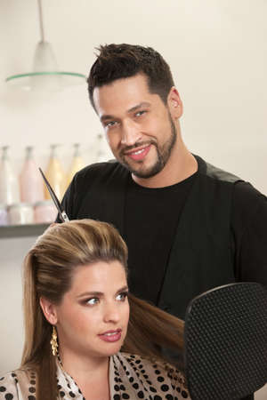 Attractive male Hispanic hairdresser with smiling customer photo