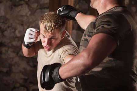 agachado: Rubio luchador de MMA esquiva un golpe oponente y golpea Foto de archivo