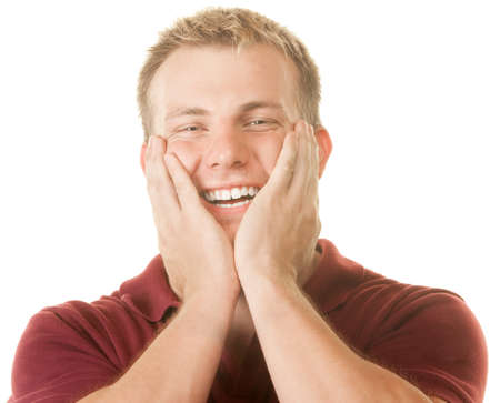 flattered: Smiling young man with hands on face over white Stock Photo