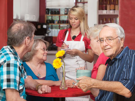 senior group: Senior Caucasian male sitting with friends in a cafe