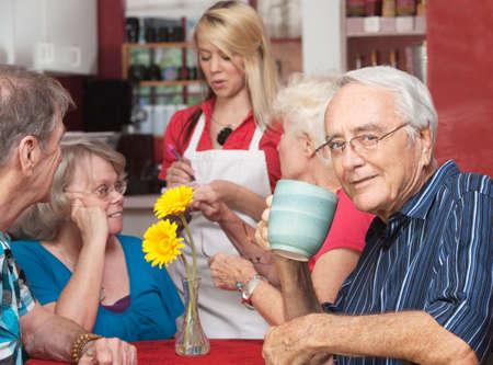 hombre tomando cafe: Hombre maduro el consumo de caf� mientras que los amigos orden en el caf�