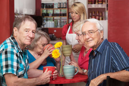 ordering: Cheerful group of senior citizens in cafe ordering drinks