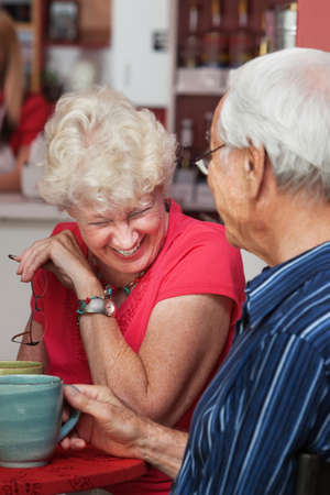 Older Caucasian woman laughing at table with man photo