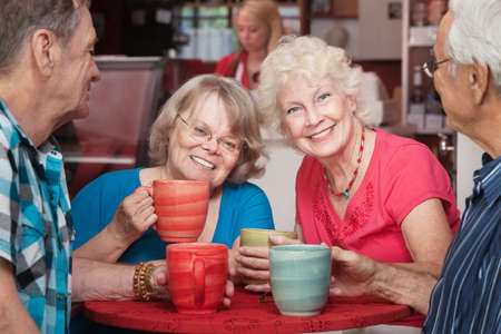 Senior female friends smiling at cafe with group