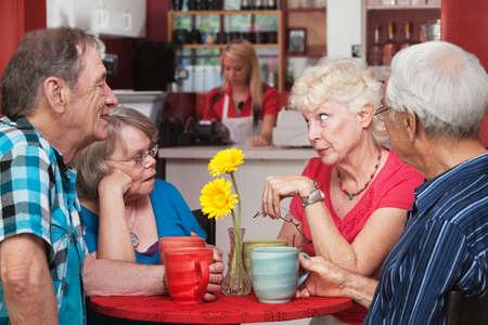 Bezorgde vrouw in gesprek met vrienden in bistro Stockfoto