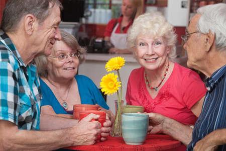 dialogo: Grupo de cuatro ciudadanos felices altos en el restaurante Foto de archivo