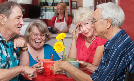 Woman holding forehead as friends laugh at the table photo