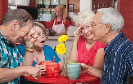 Woman cringing with group of senior friends in a cafe photo