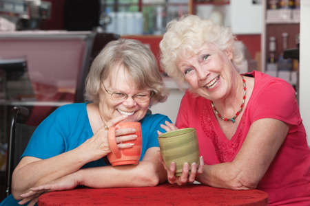 Two smiling senior friends holding coffee mugs photo