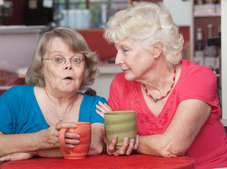 suspense: Surprised older woman talking with her friend in a cafe Stock Photo